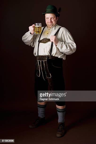 Stereotypical German man in Bavarian costume raising a beer in toast