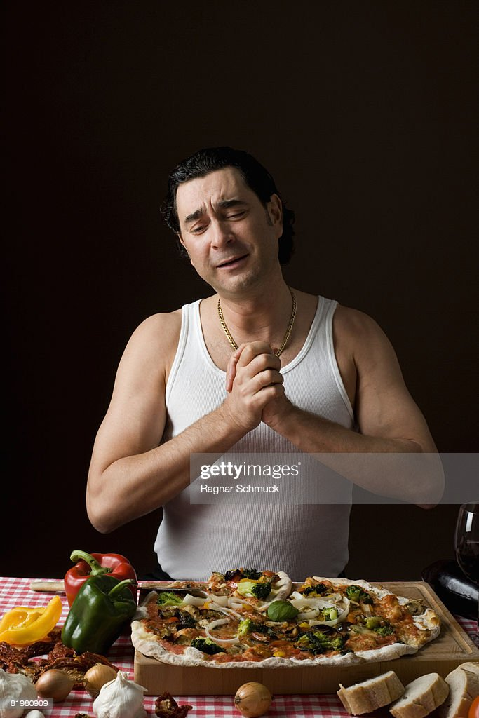 Stereotypical Italian man with hands clasped in gratitude looking at a pizza