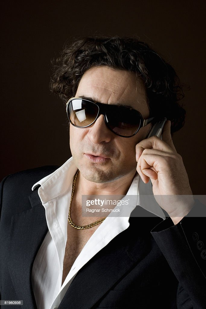Stereotypical macho, sleazy man talking on a mobile phone