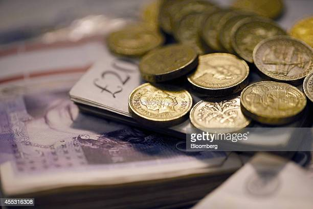 Sterling one pound coins and bundles of 20 pound sterling banknotes are arranged for a photograph inside a Travelex store operated by Travelex...