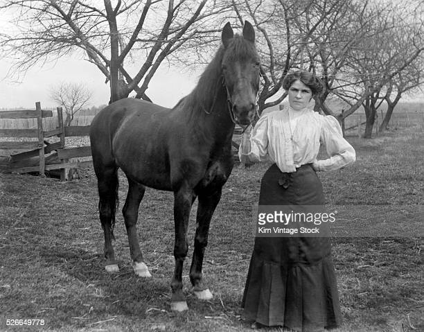 A stern looking woman holds her horse for a portrait