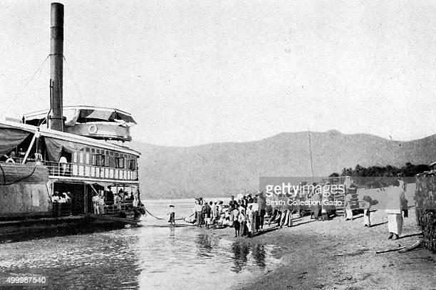 Stern wheeler river boat taking on passengers on the upper Chindwin River Myanmar 1922