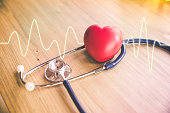 red rubber heart and stethoscope with cardiogram on wood background, health concept