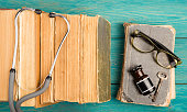 Old medical books with stethoscope, glasses, bottle and key on blue wooden background
