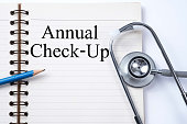 Stethoscope on notebook and pencil with Annual Check-Up words as medical concept.