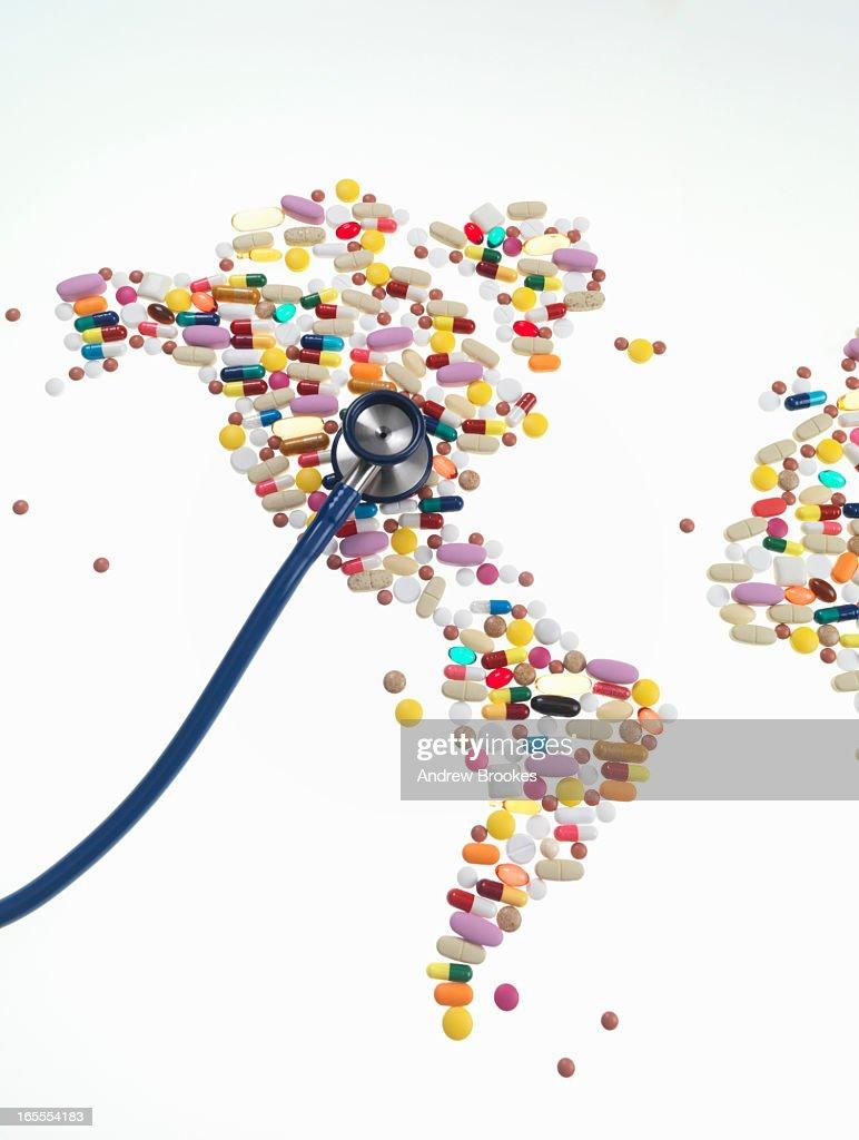 Stethoscope on pills in world map shape : Stock Photo