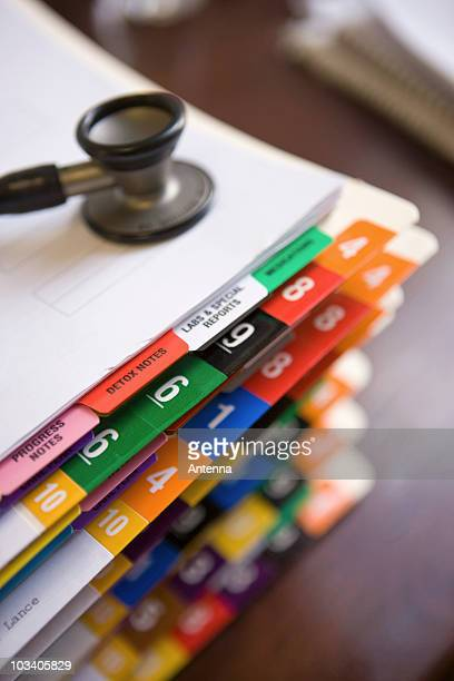 A stethoscope on top of a stack of patient files