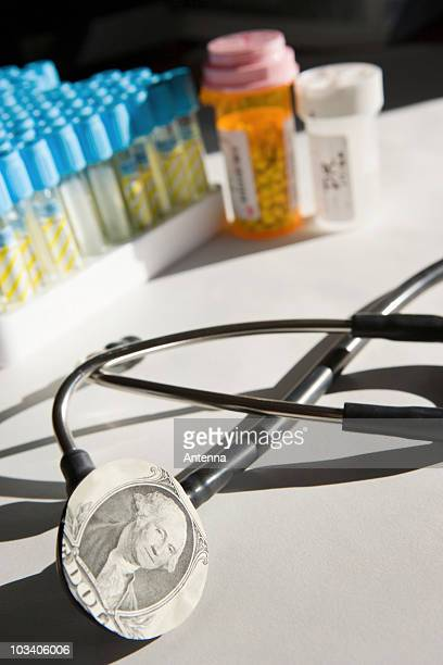 A stethoscope with a dollar bill on it and medicine in the background