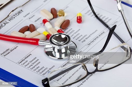 Stethoscope with eyeglasses and pills laying in a medical form : Stock Photo