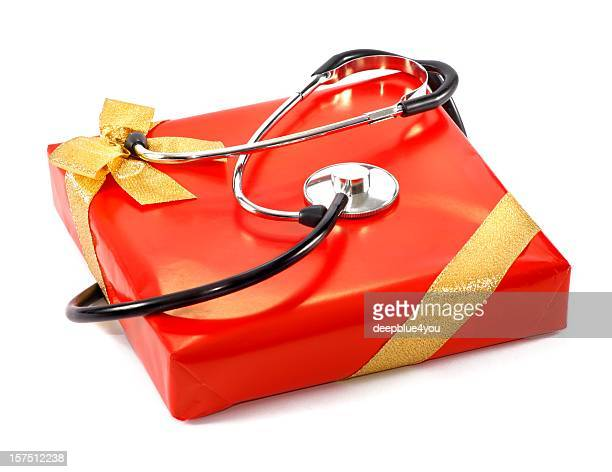 Stethoskop on a red gift box with golden loop isolated