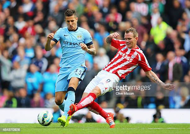 Stevan Jovetic of Manchester City is tackled by Glenn Whelan of Stoke City during the Barclays Premier League match between Manchester City and Stoke...