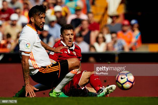 Stevan Jovetic of Sevilla FC competes for the ball with Ezequiel Garay of Valencia CF during the La Liga match between Valencia CF and Sevilla FC at...