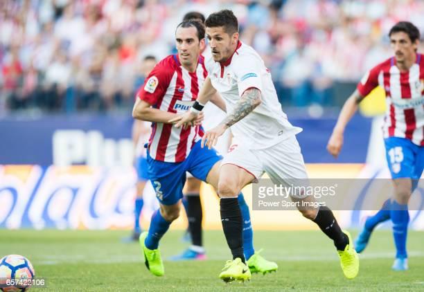 Stevan Jovetic of Sevilla FC runs past Diego Roberto Godin Leal of Atletico de Madrid during their La Liga match between Atletico de Madrid and...