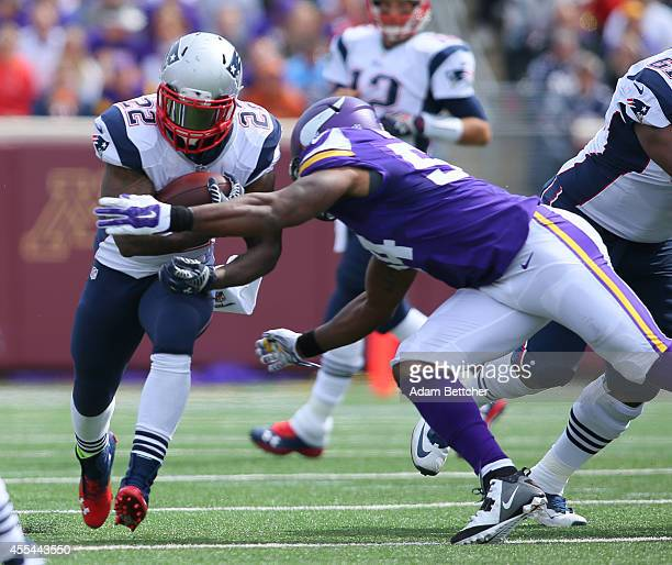 Stevan Ridley of the New England Patriots carries the ball for a gain in the second quarter while Jasper Brinkley of the Minnesota Vikings makes the...