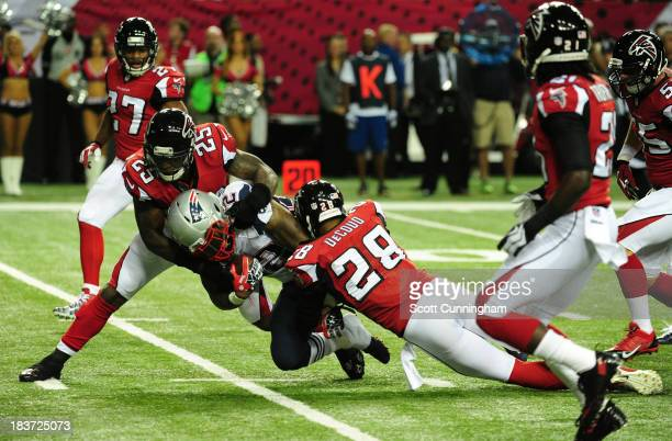 Stevan Ridley of the New England Patriots is tackled by William Moore and Thomas DeCoud of the Atlanta Falcons at the Georgia Dome on September 29...