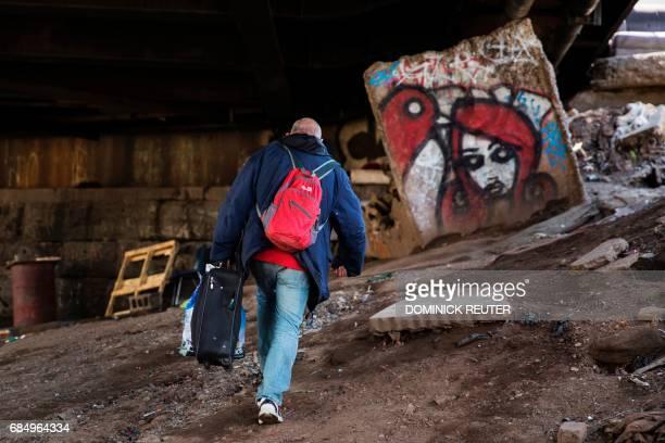 Steve an addict walks up to the street after getting high at a heroin encampment in the Kensington neighborhood of Philadelphia Pennsylvania on April...