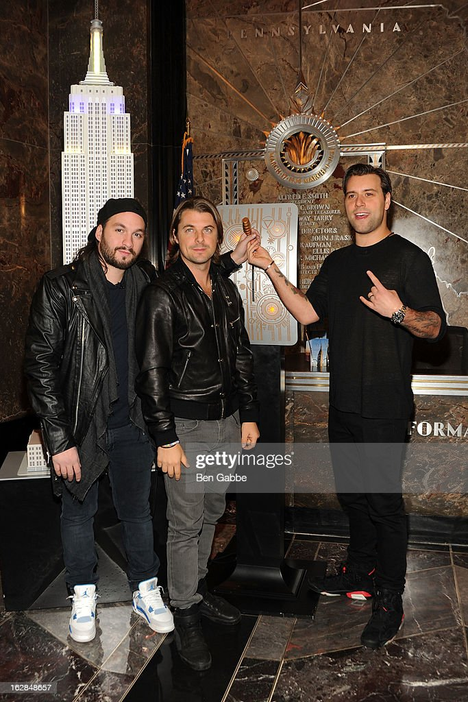 Steve Angello, Axwell and Sebastian Ingrosso of the Swedish House Mafia light The Empire State Building on February 28, 2013 in New York City.