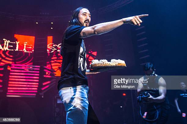 Steve Aoki performs throwing cake into the crowd onstage during a date of his Neon Future tour at Brixton Academy on April 4 2014 in London England