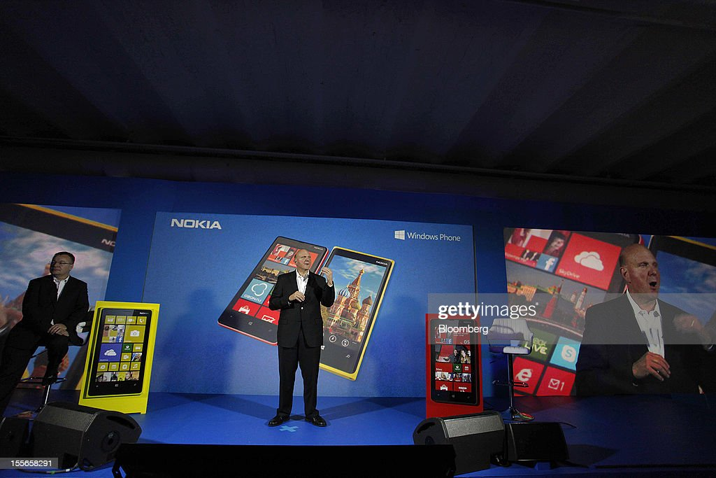 Steve Ballmer, chief executive officer of Microsoft Corp., center, speaks while Stephen Elop, chief executive officer of Nokia Oyj, left, listens during a presentation of the new Nokia Lumia 920 smartphone at a news conference in Moscow, Russia, on Tuesday, Nov. 6, 2012. Microsoft is considering building mobile hardware as a backup, in the event that its current approach of providing software to handset makers such as Nokia Oyj and HTC Corp. falters, said the people, who requested anonymity because the plans are private. Photographer: Alexander Zemlianichenko Jr./Bloomberg via Getty Images