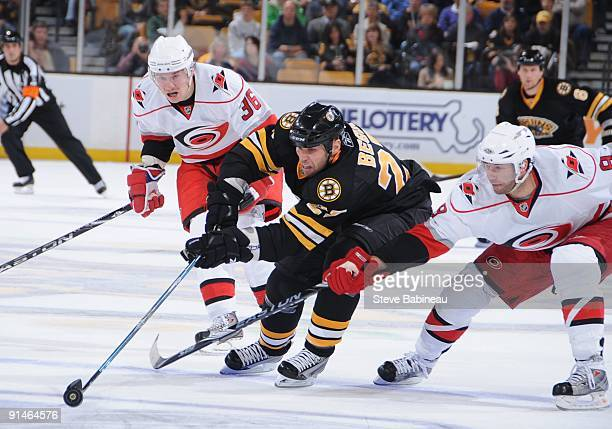 Steve Begin of the Boston Bruins skates after the puck against Jussi Jokinen and Matt Cullen of the Carolina Hurricanes at the TD Banknorth Garden on...