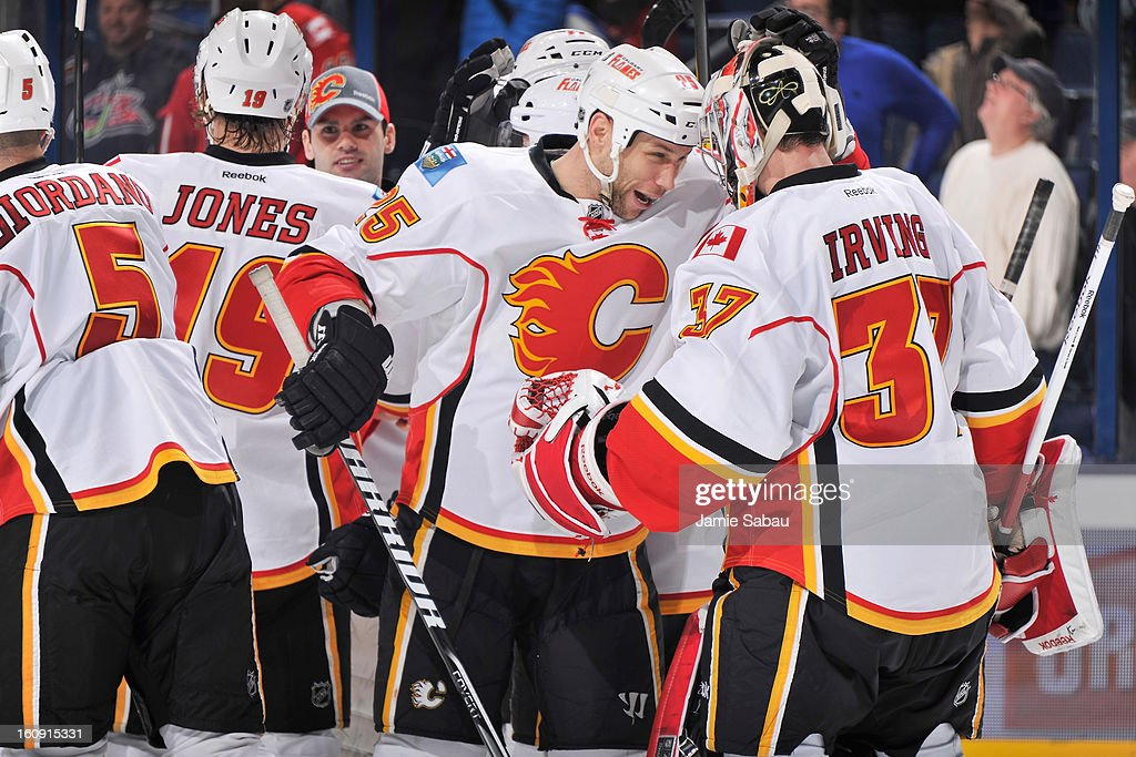 Steve Begin #25 of the Calgary Flames congratulates goaltender Leland Irving #37 of the Calgary Flames after Leland earned his first win of the season against the Columbus Blue Jackets on February 7, 2013 at Nationwide Arena in Columbus, Ohio. Calgary defeated Columbus in overtime 4-3.