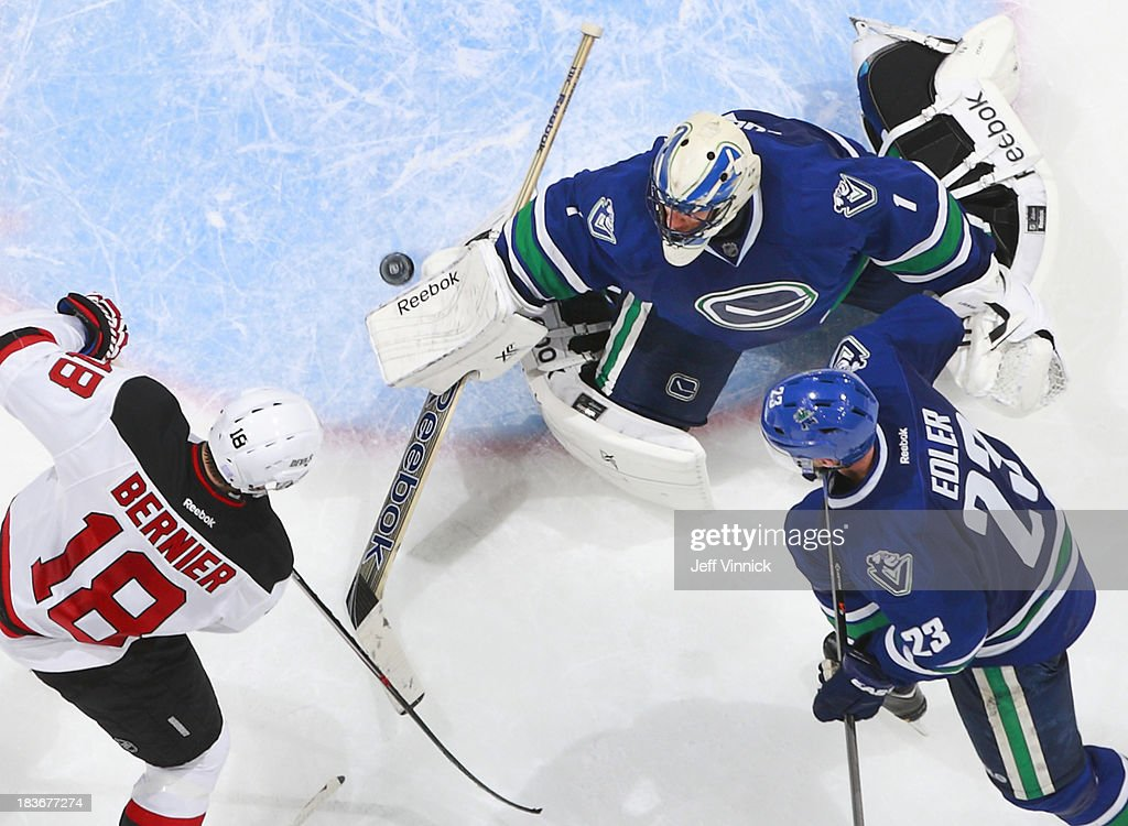 <a gi-track='captionPersonalityLinkClicked' href=/galleries/search?phrase=Steve+Bernier&family=editorial&specificpeople=557040 ng-click='$event.stopPropagation()'>Steve Bernier</a> #18 of the New Jersey Devils and <a gi-track='captionPersonalityLinkClicked' href=/galleries/search?phrase=Alexander+Edler&family=editorial&specificpeople=882987 ng-click='$event.stopPropagation()'>Alexander Edler</a> #23 of the Vancouver Canucks watch <a gi-track='captionPersonalityLinkClicked' href=/galleries/search?phrase=Roberto+Luongo&family=editorial&specificpeople=202638 ng-click='$event.stopPropagation()'>Roberto Luongo</a> #1 of the Canucks play the puck off his blocker during their NHL game at Rogers Arena on October 8, 2013 in Vancouver, British Columbia, Canada. Vancouver won 3-2.