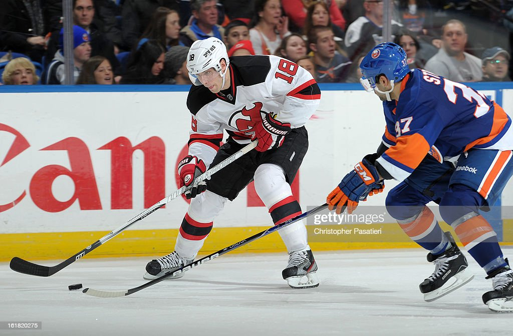 Steve Bernier #18 of the New Jersey Devils skates with the puck against Brian Strait #37 of the New York Islanders during the game on February 16, 2013 at Nassau Veterans Memorial Coliseum in Uniondale, New York.