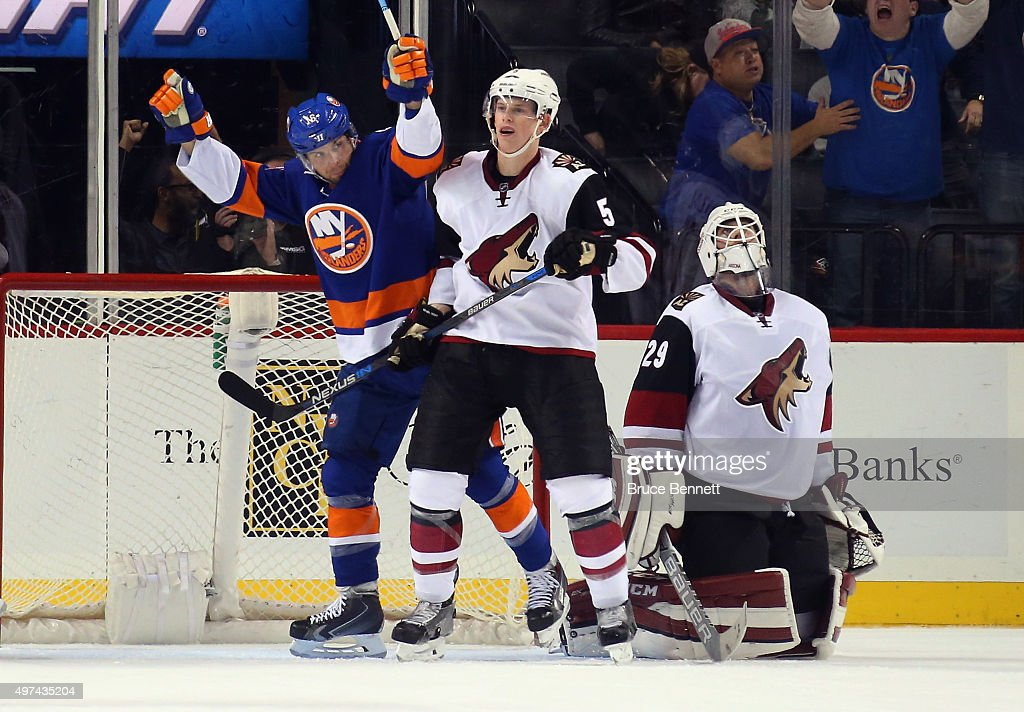 Steve Bernier of the New York Islanders celebrates his third period goal against Anders Lindback of the Arizona Coyotes as Connor Murphy looks on at...