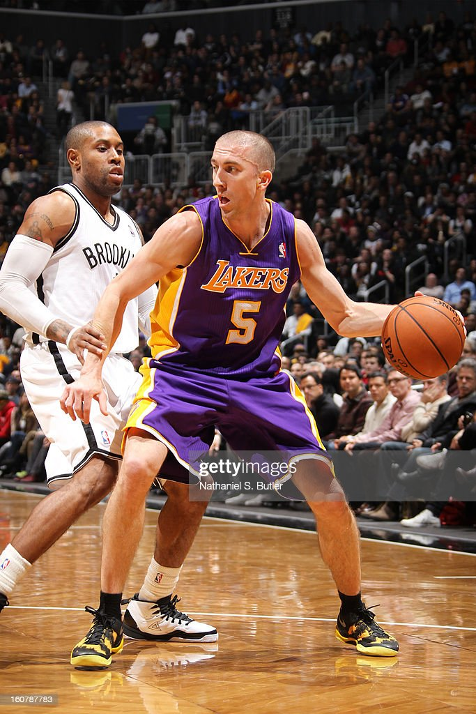 Steve Blake #5 of the Los Angeles Lakers controls the ball against C.J. Watson #1 of the Brooklyn Nets on February 5, 2013 at the Barclays Center in the Brooklyn borough of New York City.