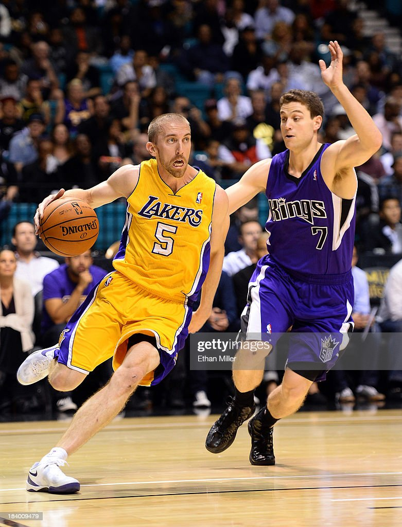 <a gi-track='captionPersonalityLinkClicked' href=/galleries/search?phrase=Steve+Blake+-+Basketball+Player&family=editorial&specificpeople=204474 ng-click='$event.stopPropagation()'>Steve Blake</a> #5 of the Los Angeles Lakers drives against <a gi-track='captionPersonalityLinkClicked' href=/galleries/search?phrase=Jimmer+Fredette&family=editorial&specificpeople=5020564 ng-click='$event.stopPropagation()'>Jimmer Fredette</a> #7 of the Sacramento Kings during their preseason game at the MGM Grand Garden Arena on October 10, 2013 in Las Vegas, Nevada. Sacramento won 104-86.