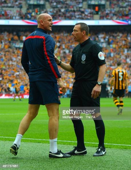 Steve Bould assistant manager of Arsenal speaks with the fourth official Kevin Friend during the FA Cup with Budweiser Final match between Arsenal...