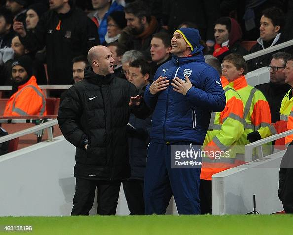 Steve Bould the Arsenal Assistant Manager shares a joke with Anthony Taylor the 4th Official during the match between Arsenal and Leicester City in...