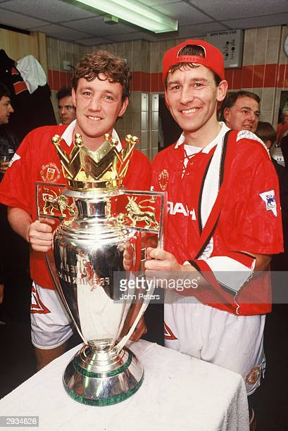 Steve Bruce and Bryan Robson celebrate with the Premiership Trophy in the dressing room after the FA Carling Premiership Match between Manchester...