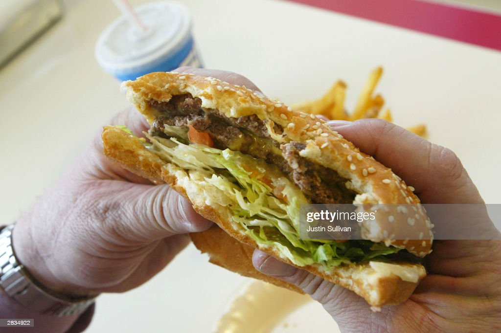 Steve Calhoun prepares to bite into a double cheeseburger at Majors Hamburgers December 28 2003 in Yakima Washington Two farms have been quarantined...