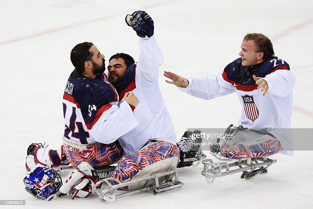 Steve Cash of the USA and Nikko Landeros of the USA and Joshua Pauls of the USA celebrate after winning the ice sledge hockey gold medal game between the Russian Federation and the United States of America at the Shayba Arena during day eight of the 2014 Paralympic Winter Games on March 15, 2014 in Sochi, Russia.