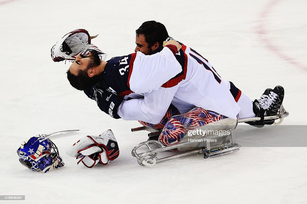 Steve Cash of the USA and Nikko Landeros of the USA celebrate after winning the ice sledge hockey gold medal game between the Russian Federation and the United States of America at the Shayba Arena during day eight of the 2014 Paralympic Winter Games on March 15, 2014 in Sochi, Russia.