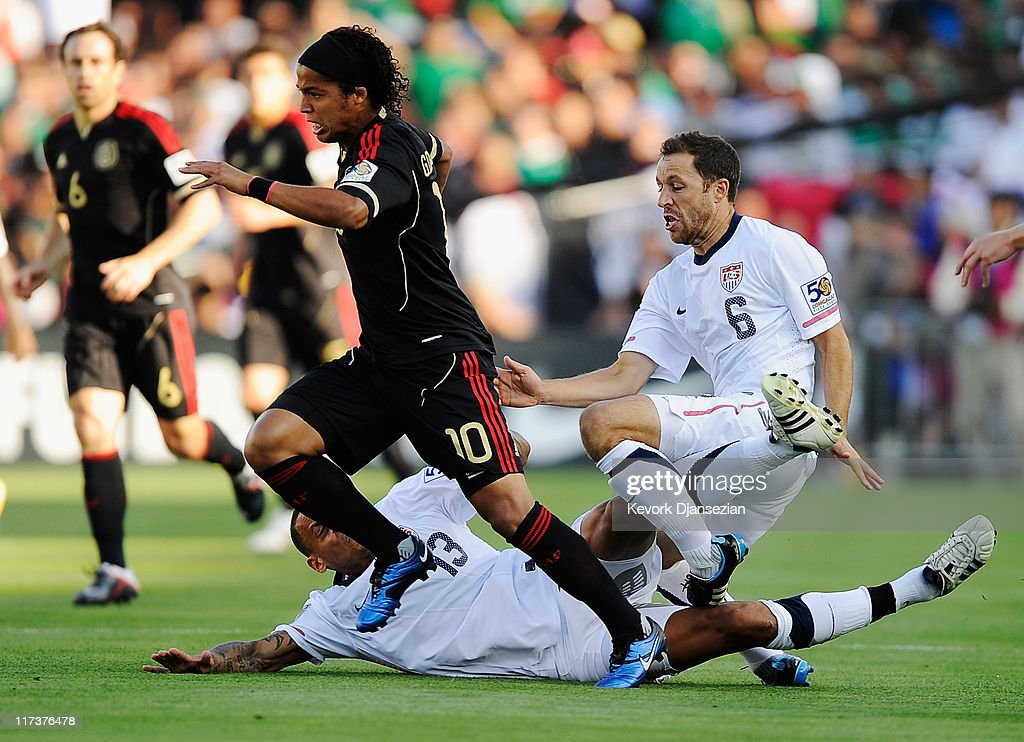 Steve Cherundolo of the United States injures his ankle as he collides with teammate Jermaine Jones as they were defending Giovanni Dos Santos of...
