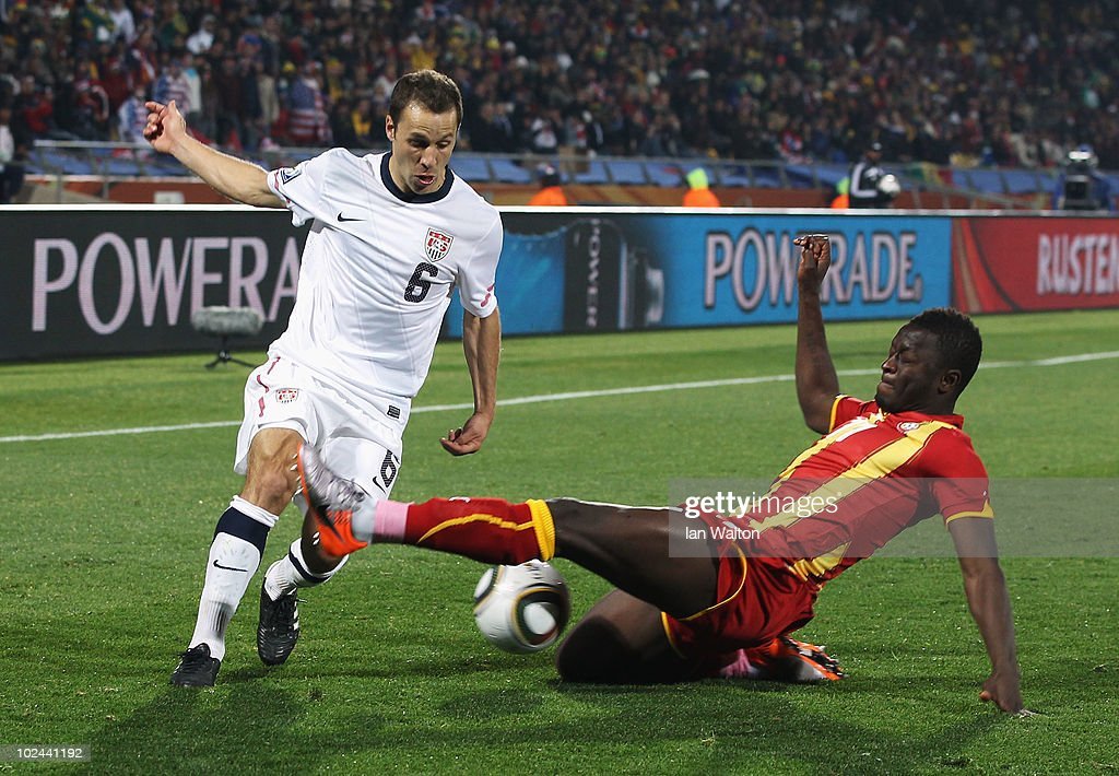 Steve Cherundolo of the United States is challenged by Sulley Muntari of Ghana during the 2010 FIFA World Cup South Africa Round of Sixteen match...