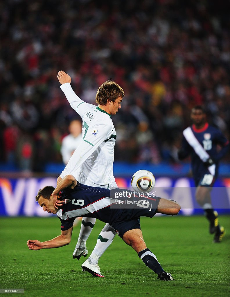 Steve Cherundolo of the United States is tackled by Nejc Pecnik of Slovenia during the 2010 FIFA World Cup South Africa Group C match between...