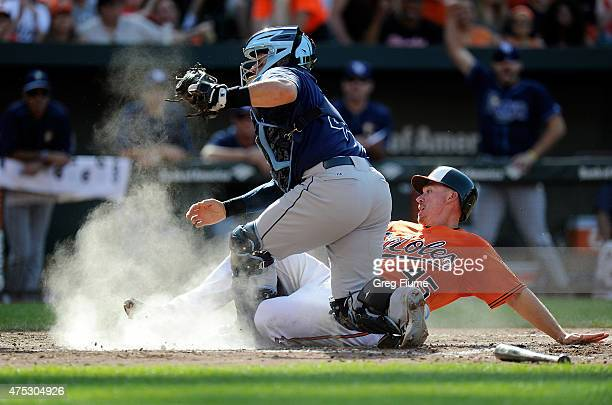 Steve Clevenger of the Baltimore Orioles is tagged out at home plate in the fifth inning by Rene Rivera of the Tampa Bay Rays at Oriole Park at...