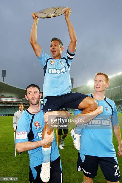 Steve Corica of Sydney holds the Minor Premiership trophy as he is chaired around the field during the round 27 ALeague match between Sydney FC and...