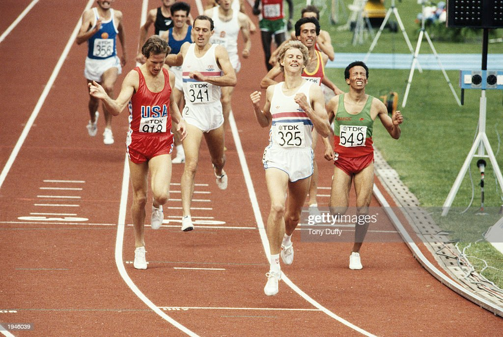 Steve Cram of Great Britain crosses the finishing line to win the 1500 metres final from Steve Scott of the USA and Said Aouita of Morrocco during...
