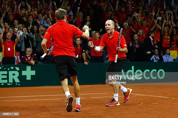 Steve Darcis and David Goffin of Belgium celebrate winning the second set against Jamie Murray and Andy Murray of Great Britain in the doubles during...