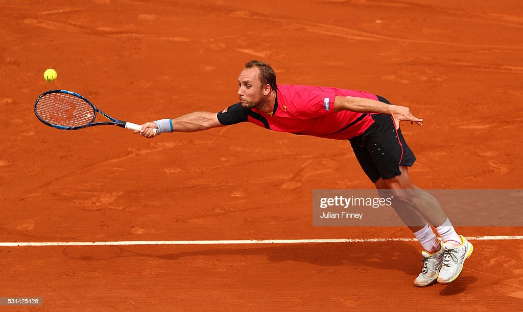Steve Darcis of Belgium stretches to hit a forehand during the Men's Singles second round match against Novak Djokovic of Serbia on day five of the 2016 French Open at Roland Garros on May 26, 2016 in Paris, France.