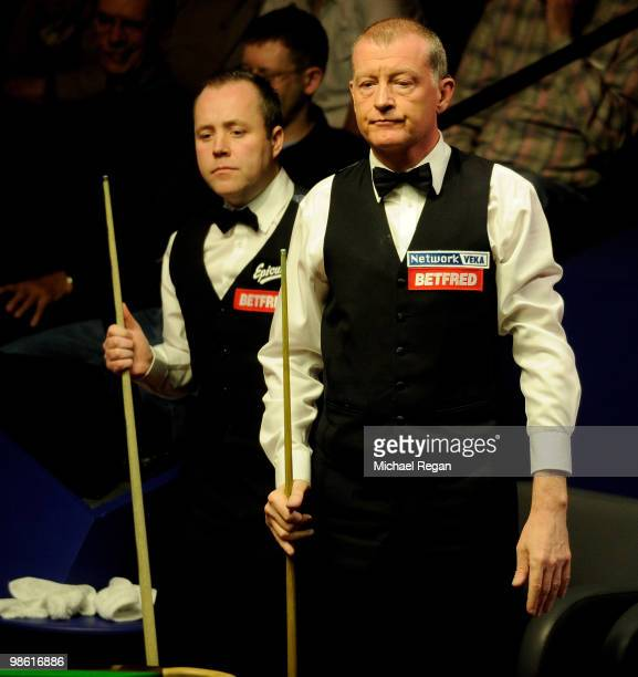 Steve Davis of England and John Higgins of Scotland look on during the Betfredcom World Snooker Championships at the Crucible Theatre on April 22...