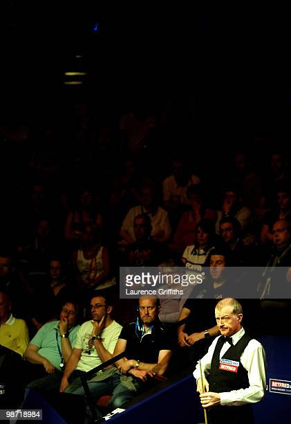 Steve Davis of England chalks his cue against Neil Robertson of Australia during the Quarter Finals of the Betfredcom World Snooker Championships at...