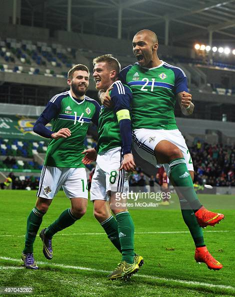 Steve Davis of Northern Ireland celebrates with teammates Stuart Dallas and Josh MaGennis after scoring during the international football friendly at...