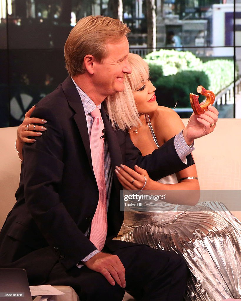 Steve Doocy enjoys a cronut from Rita Ora as she visits 'Fox & Friends' at the FOX Studios on August 19, 2014 in New York City.