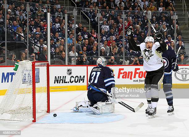 Steve Downie of the Pittsburgh Penguins throws his arms in celebration after a shot by teammate Simon Despres gets past goaltender Ondrej Pavelec of...
