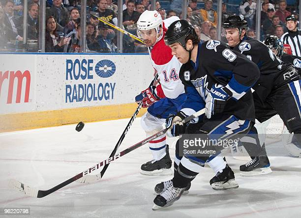 Steve Downie of the Tampa Bay Lightning battles for the puck against Tomas Plekanec of the Montreal Canadiens at the St Pete Times Forum on January...